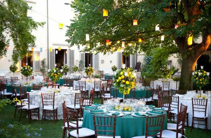 tischdekoration geburtstag, blaue und weiße tischdecken, harmonische gestaltung, gelbe blumen auf dem tisch und leuchten an den bäumen