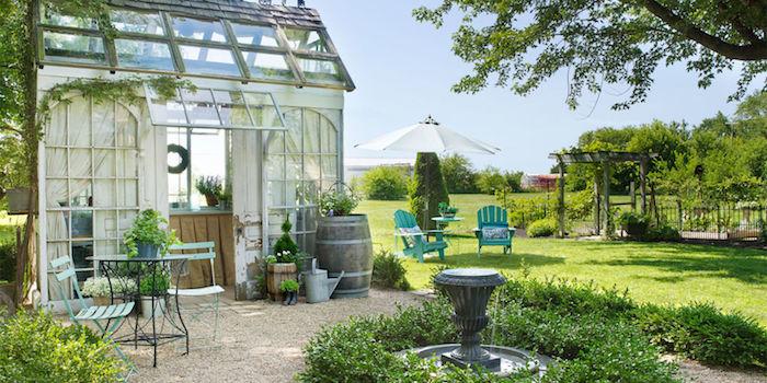 gartenplanung beispiele, sonnenschirm, zwei blaue stühle aus holz, wiesen, gartenhaus