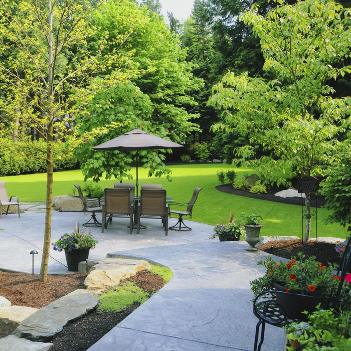 bequeme Stühle und Esstisch, Ampelschirm, ein schöner Rasen, rote Blumen, Garten verschönern