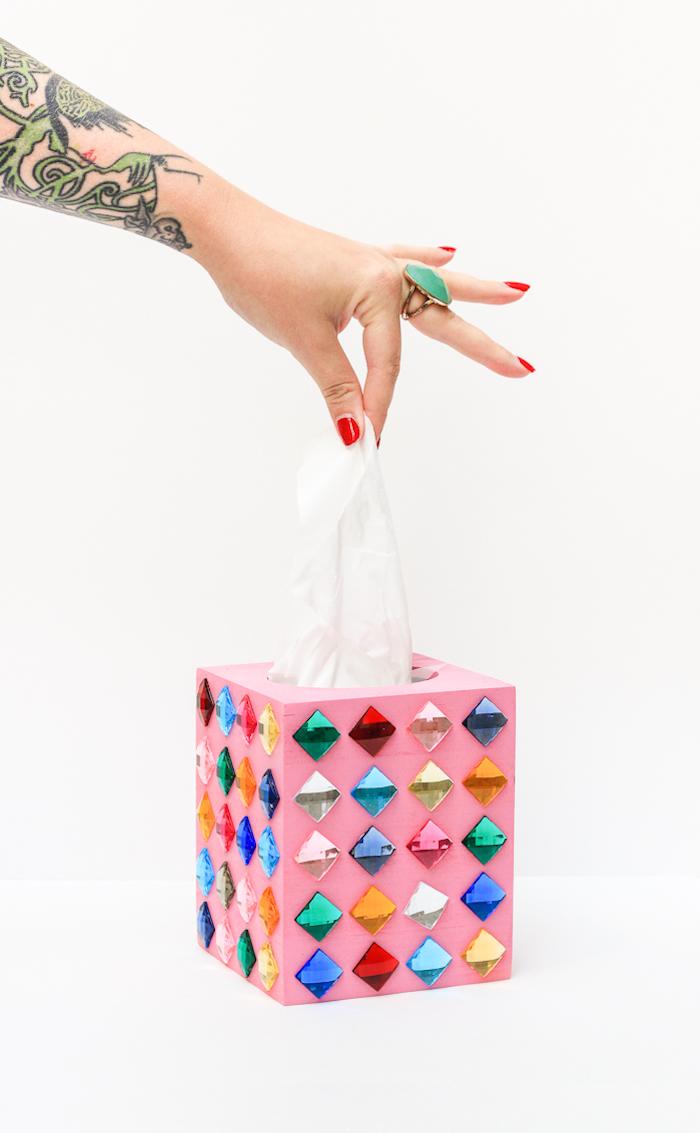 Rosa Servietten Box mit bunten Kristallen, roter Nagellack, Ring mit großem grünem Stein, Tattoos am Arm