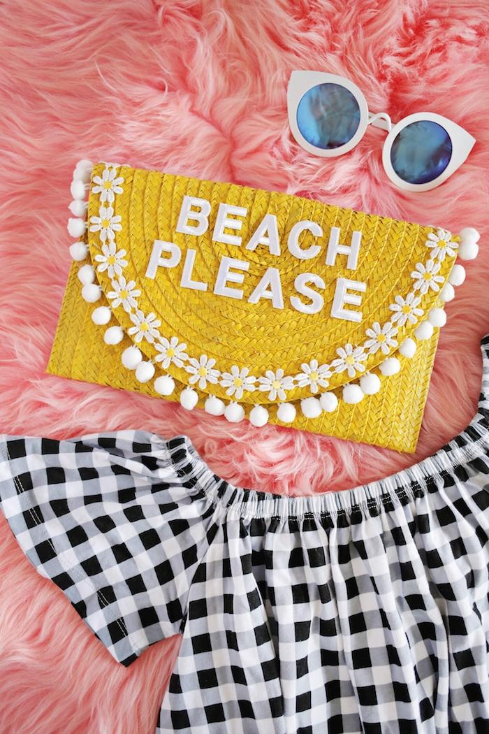 Gelbe Clutch mit Aufschrift Beach Please, weiße Pompons und kleine Blumen