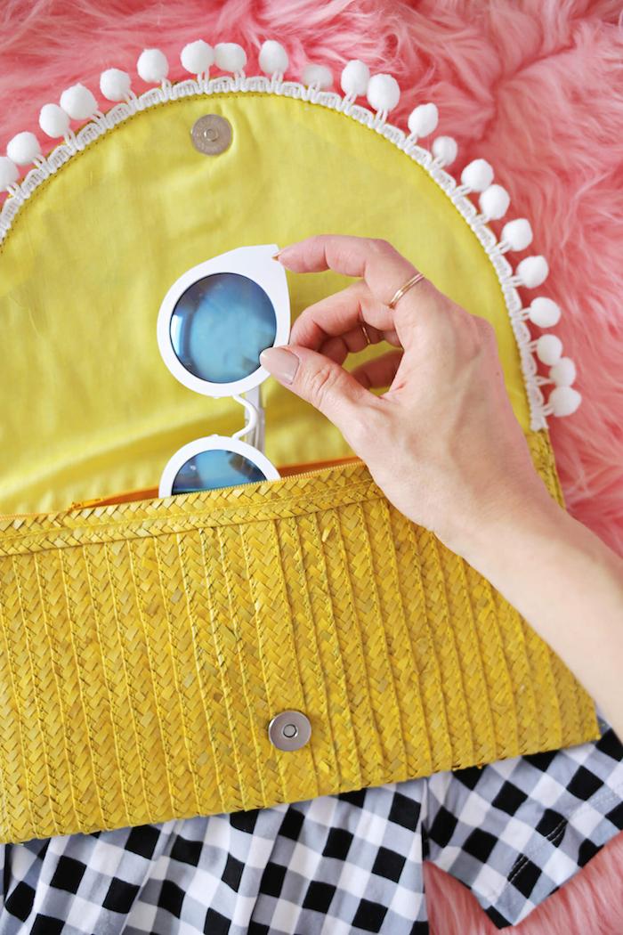Gelbe Clutch mit weißen Pompons, Sonnenbrille darin, kariertes Hemd, rosa Decke