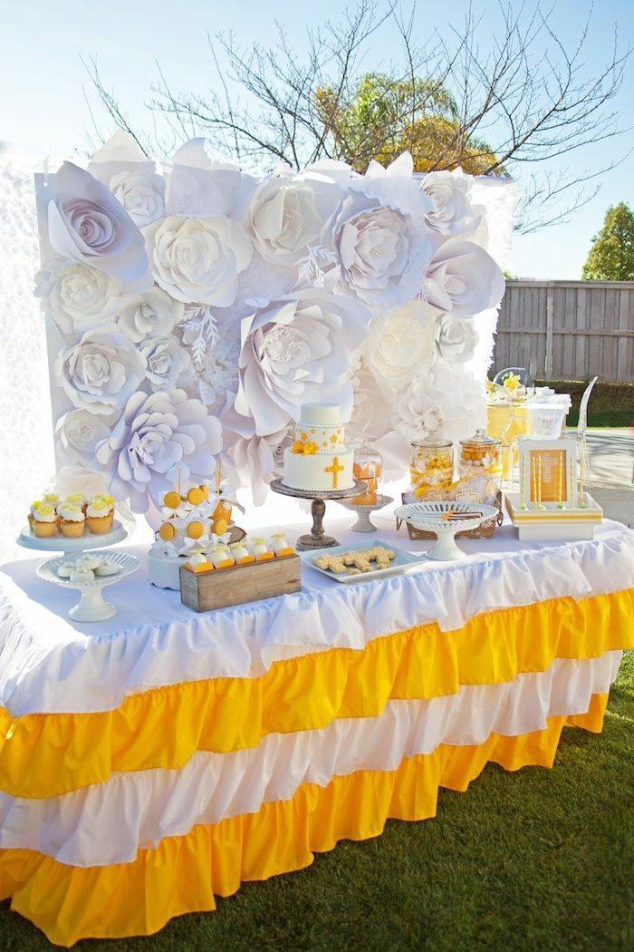 eine Torte mit Kreuz, weiße und gelbe Tischdecke, Papierblumen, Kommunion Tischdekoration