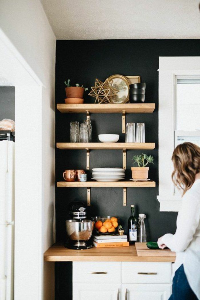 Regale auf Holz voller Geschirr und Dekoelemente, schwarze Küchenwand