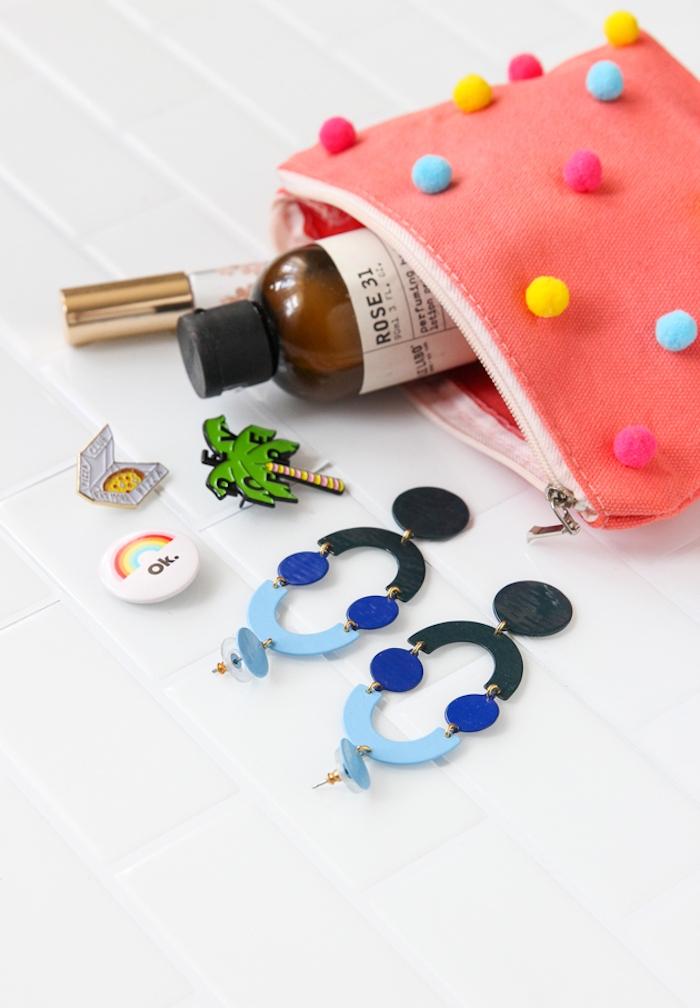 Clutch mit bunten Pompons, blaue große Ohrringe und kleine Abzeichen