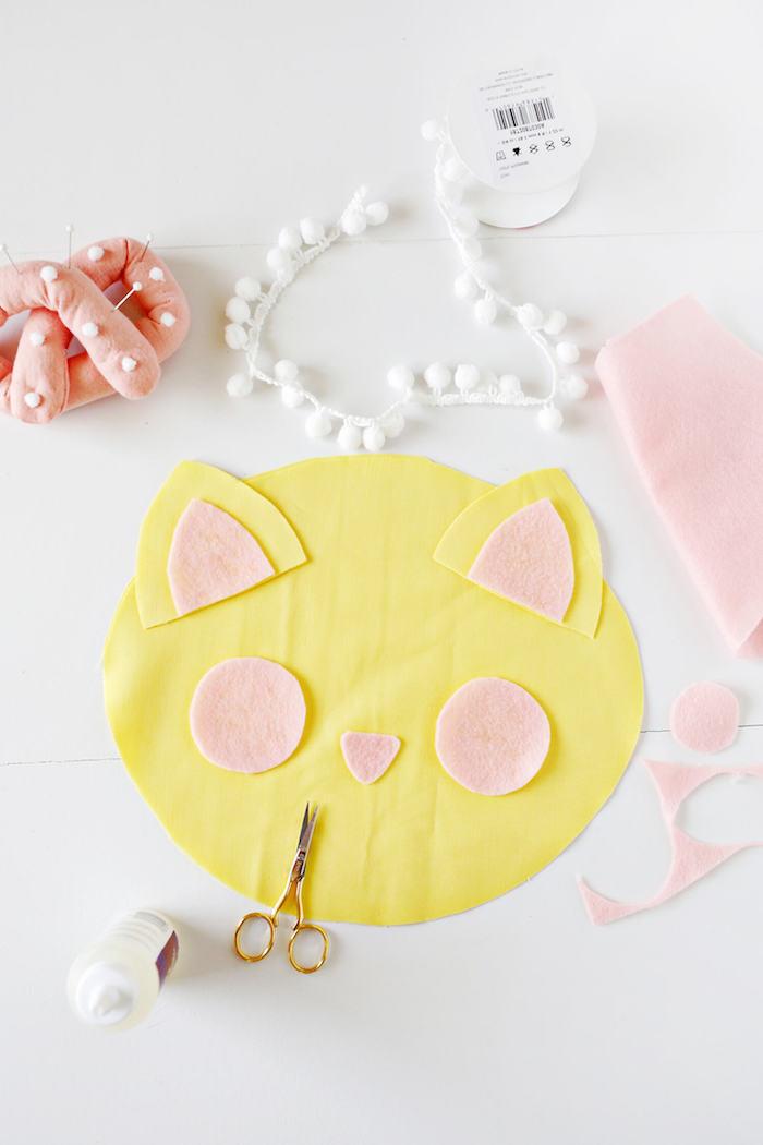 Süßes Kissen Katze selber nähen, aus gelbem Stoff, mit weißen Pompons verzieren