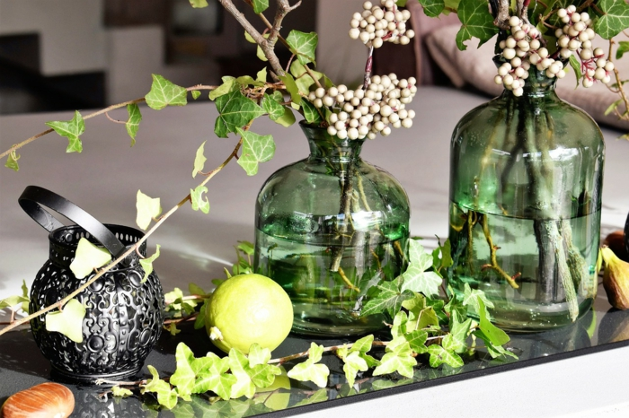 Efeu Dekoration, zwei Flaschen voller Wasser, kleine weiße Früchte, Kommunion Tischdekoration