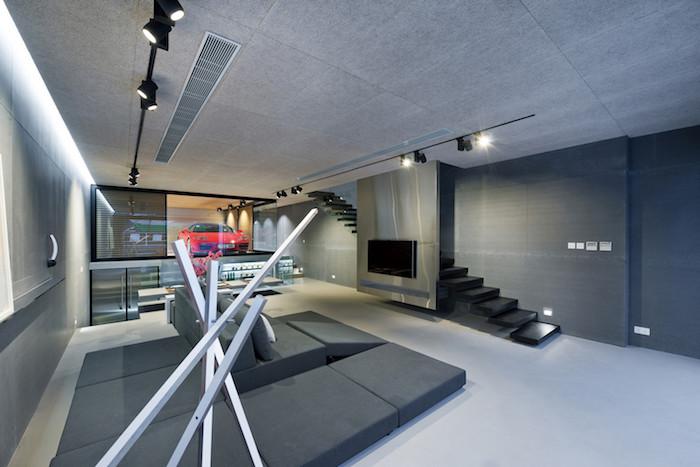 eine schwarze treppe und ein sofa mit grauen kissen, ein großes wohnzimmer mit schwarzen lampen und mit einem großen schwarzen fernseher und einem roten wagen, ein haus einrichten