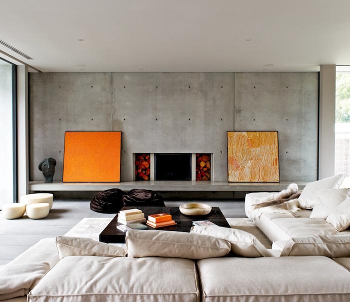 zwei orange bilder und eine große graue wand, zimmer einrichten ideen, ein sofa mit weißen großen kissen und ein kleiner schwarzer tisch mit weißen und orangen büchern