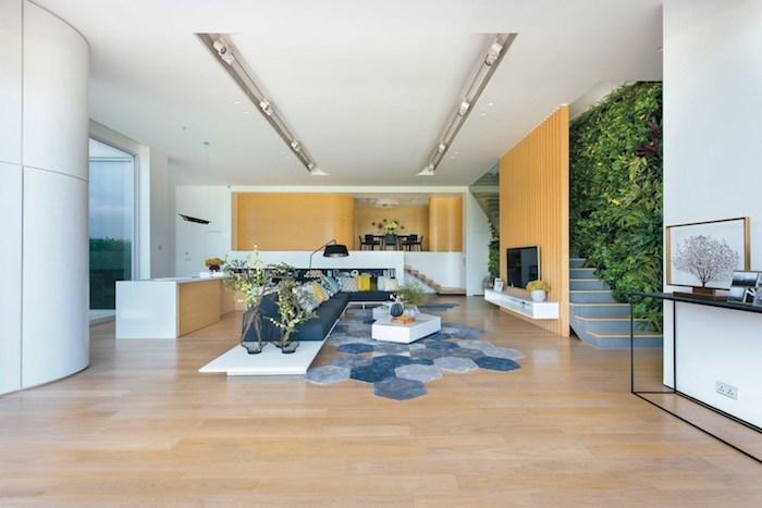 ein boden aus holz und eine graue treppe, eine wand mit pflanzen mit grünen blättern, vasen mit bluemn und grünen pflanzen