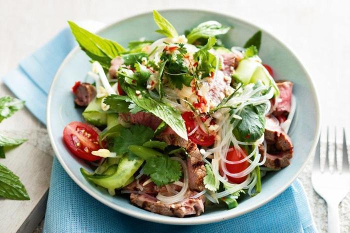 Gesunde Salate, Rucola, Kirschtomatem, einige Stück Fleisch, Zwiebel auf Scheiben