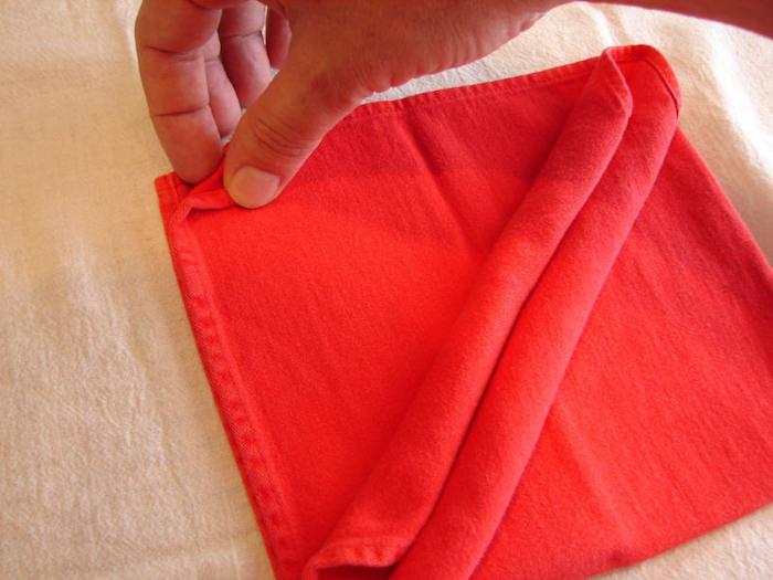 eine hand und eine gefaltete rote bestecktasche, servietten falten anleitung, tischdeko selber machen
