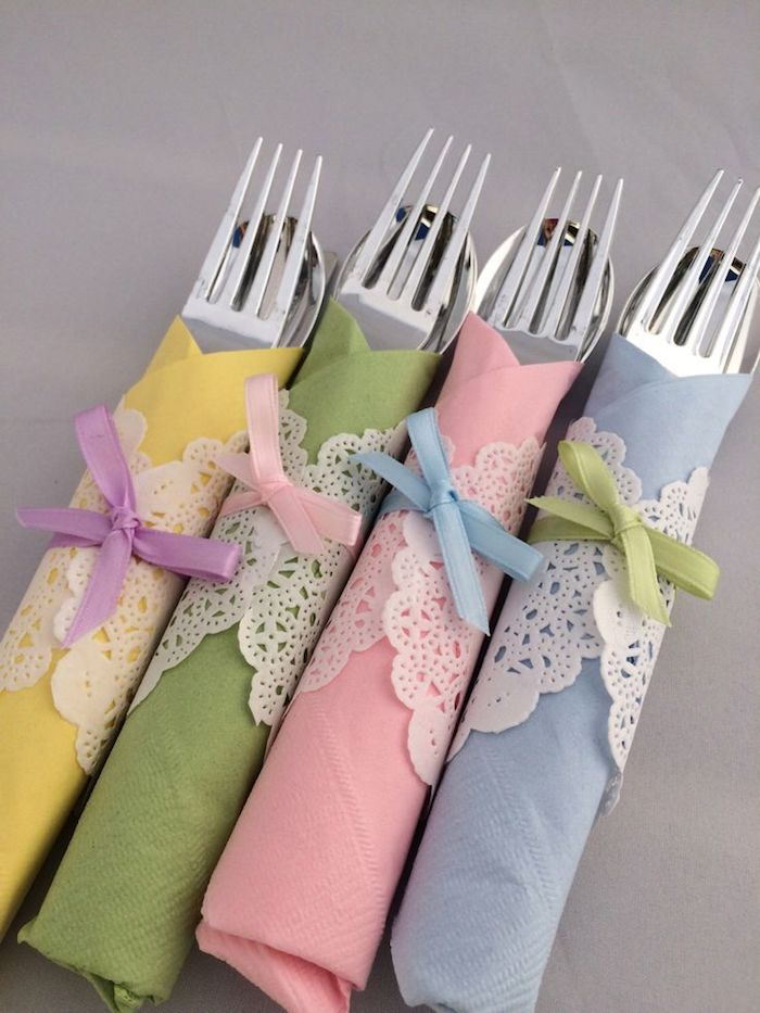 vier gelbe, grüne, pinke und blaue bestecktaschen aus servietten und mit vier gabeln und messern, kleine violetten, pinken, blauen und grünen schleifen, tischdekoration selber machen