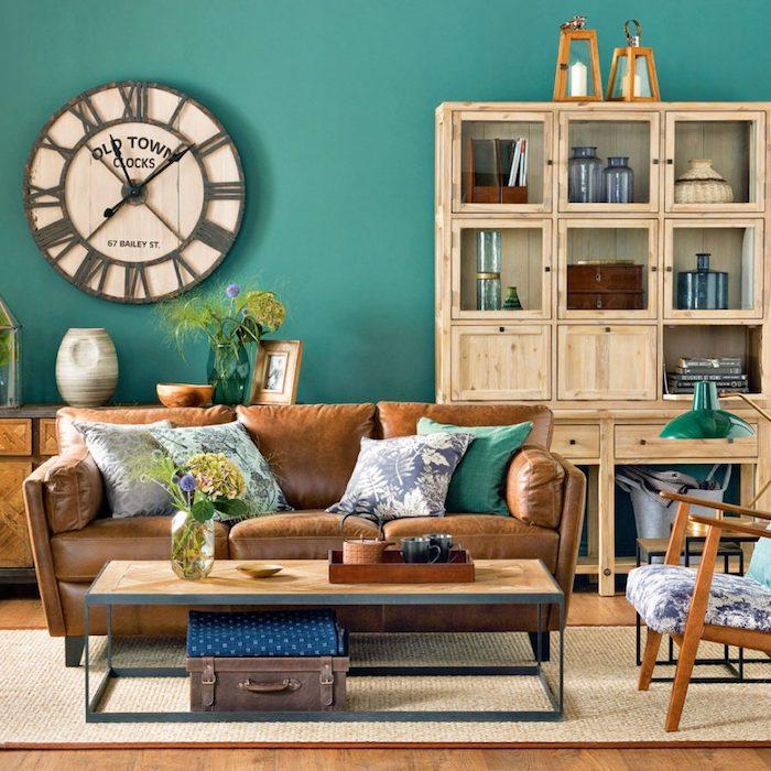 Wohnzimmer in Landhausstil, braunes Ledersofa, Schrank aus Massivholz, bunte Deko Kissen, große Wanduhr