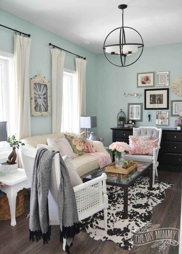 Wohnzimmer in Türkis, runder Kronleuchter, weiße Vorhänge, weißes Sofa, Kissen mit Blumenmuster