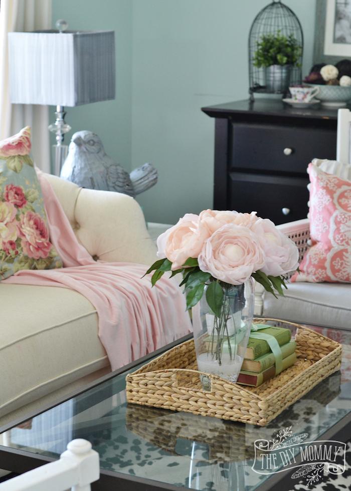 Wohnzimmer in Landhausstil, Wandfarbe Türkis, weißes Sofa, Deko Kissen mit Blumenmuster, Rosenstrauß in Glasvase