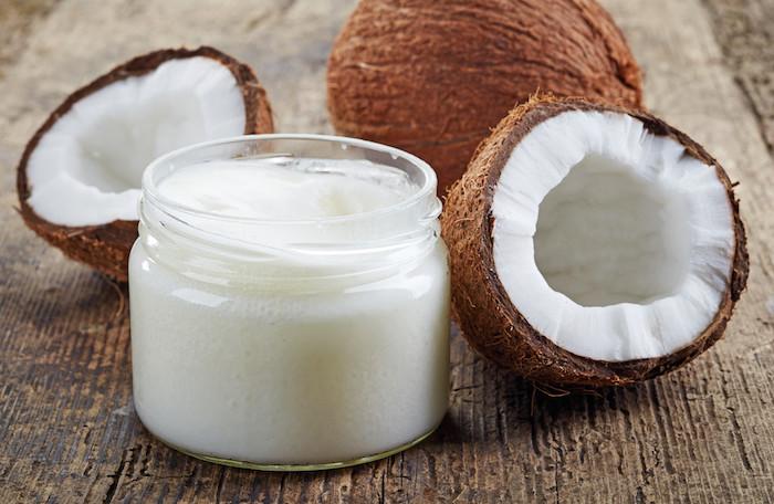 haarwachstum beschleunigen, kosmetikbehälter mit kokosöl, kokos, hölzerner tisch, haare pflegen