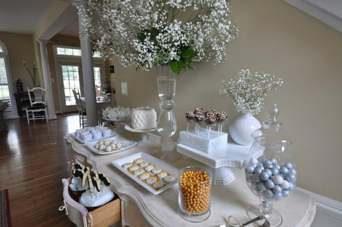 Plätzchen, goldene Bonbons, eine weiße Torte, Vase aus Glas mit weißen Blumen, Kommunion Dekoration