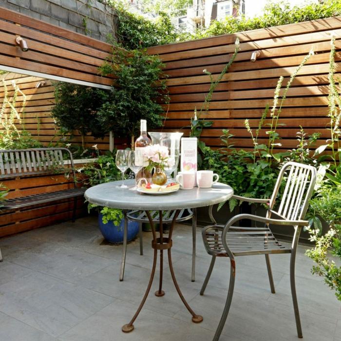 Garten verschönern, hoher Sichtschutz mit Pfanzen darüber, ein gedeckter Tisch, Pflanzkübeln