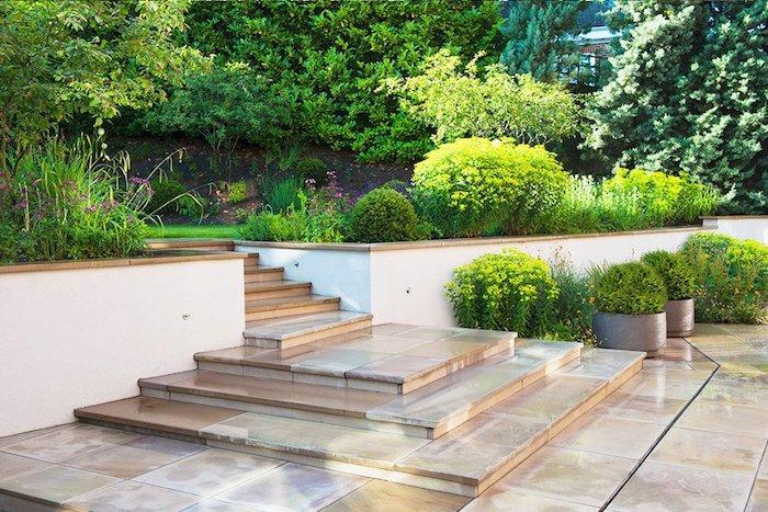 ideen gartengestaltung, treppe mit beige flisen, runde grüne büsche, gartenpflanzen
