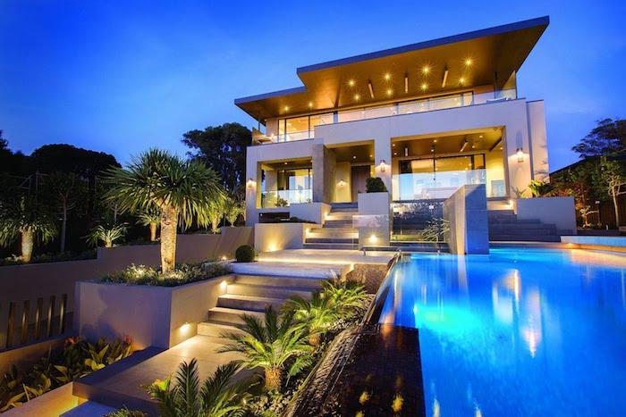 ideen gartengestaltung, großes luxuriöses haus mit schwimmbad, viele palmen, gartenbeleuchtung