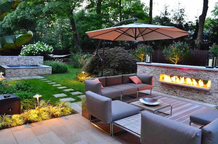 ideen gartengestaltung, großer sonnenschirm, grauer sofa mit sesseln, feuerstelle aus stein