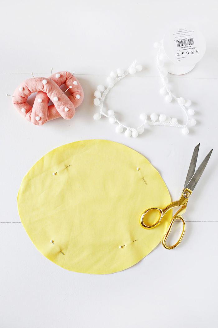 Kissen selber nähen, gelber Stoff, weiße Pompons, Nadelkissen und Schere