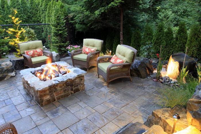 kleingarten gestalten, feuertstelle aus naturstein, sessel aus ratan mit grünen sitzkissen, sitzecke