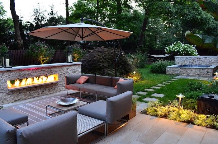 kleingarten gestalten, großer sonnenschirm, sofa mit sessel mit grauen kissen, feuerstelle aus naturstein