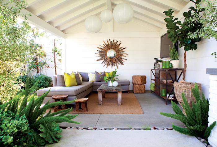 kleingarten gestalten, graues ecksofa, mit gelbern dekokissen, wanddeko, sonnenspiegel