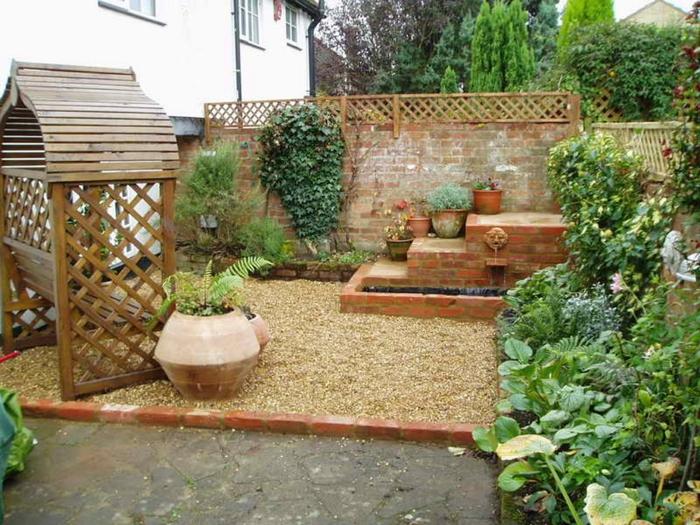 Kies Bodenbeleg, ein Wasserhahn mit Löwenkopf, grüne Pflanzen in den Ecken, Garten verschönern