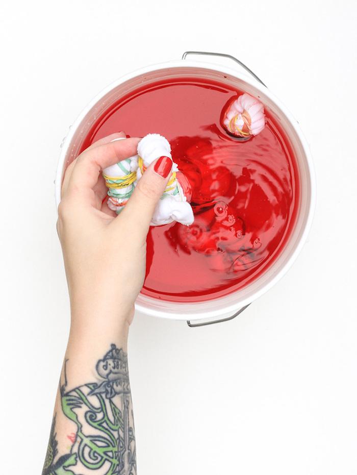Kissen selbst bemalen, im Textilfarbe eintauchen, rote Farbe, Technik mit Gummibändern