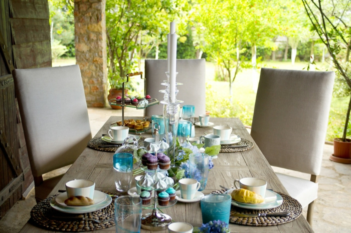 Kommunion Dekoration, drei graue Stühle, Tisch aus Holz, Cupcakes und Kerzen