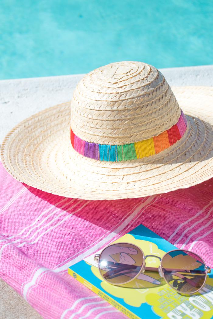 Sommerhut mit bunten Fäden verziert, Buch und Sonnenbrille, rosa Strandtuch