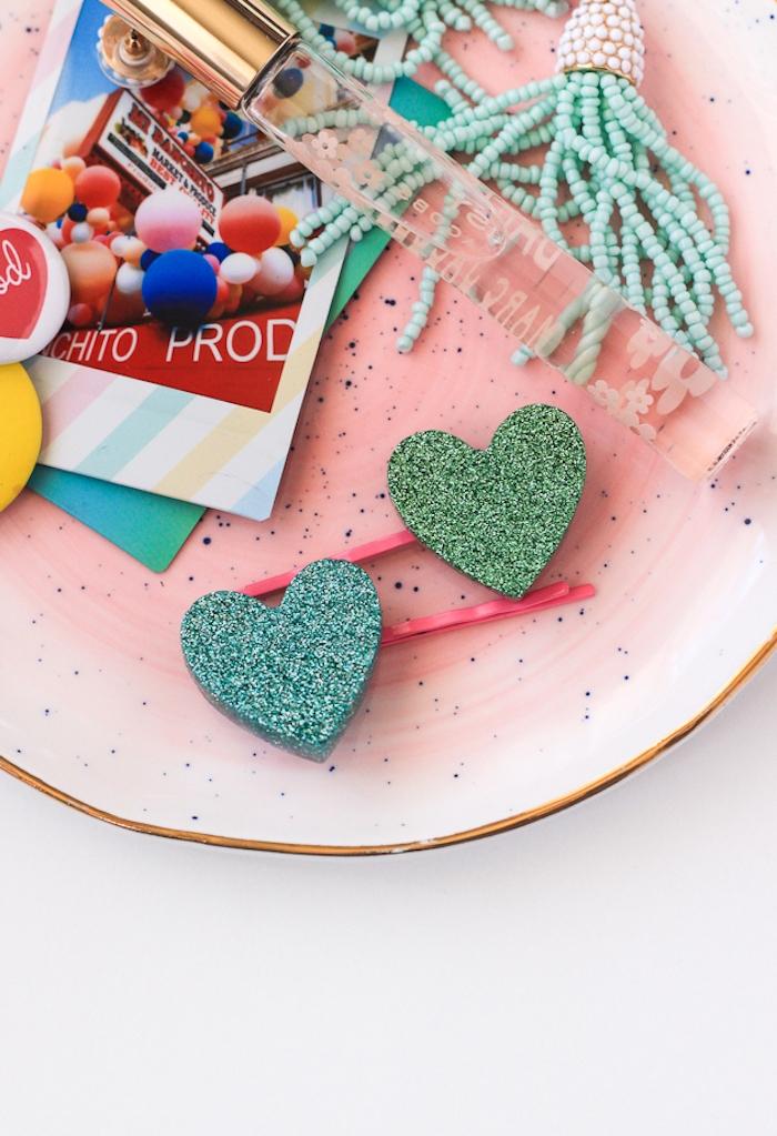 Haarklammern mit Glitterherzen in rosa Porzellanschale, blaue Perlen, Parfüm und Karten