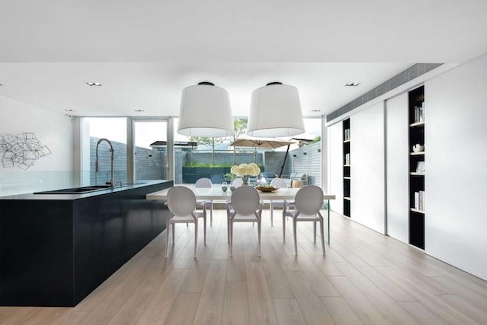 ein boden aus holz und ein weißer tisch und weiße stühle, ein wohnzimmer mit weißen wänden und mit einem großen schwarzen waschbecken und einem großen fenster und zwei weißen lampen