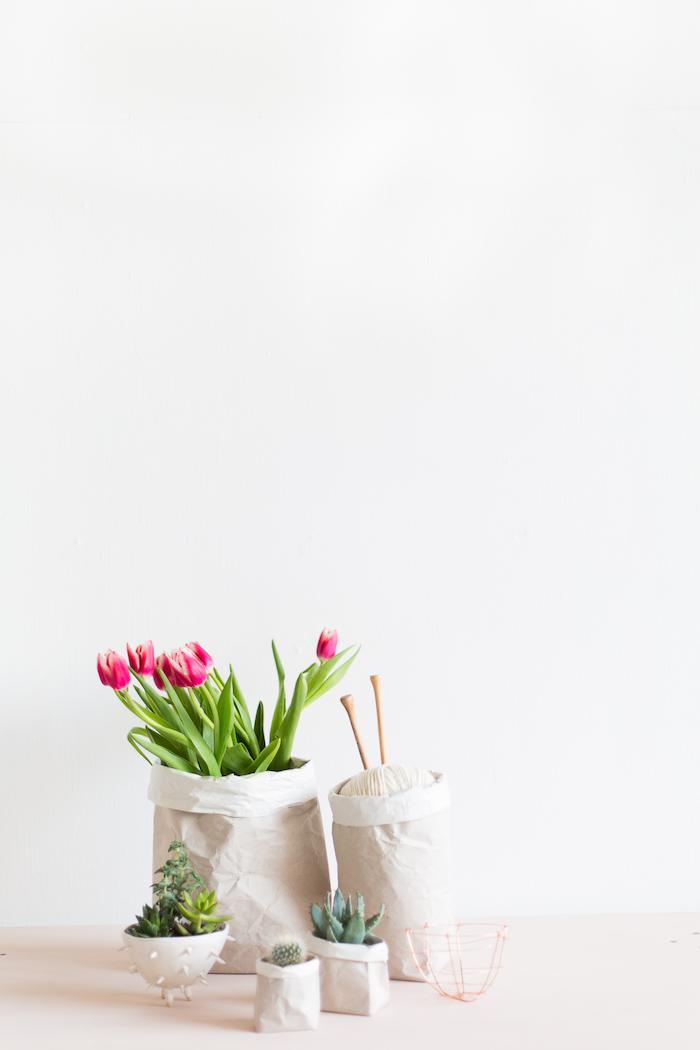 eine große weiße wand und große und kleine weiße blumentöpfe mit weißen papiertüten und mit violetten blumen mit grünen blättern und grünen kakteen