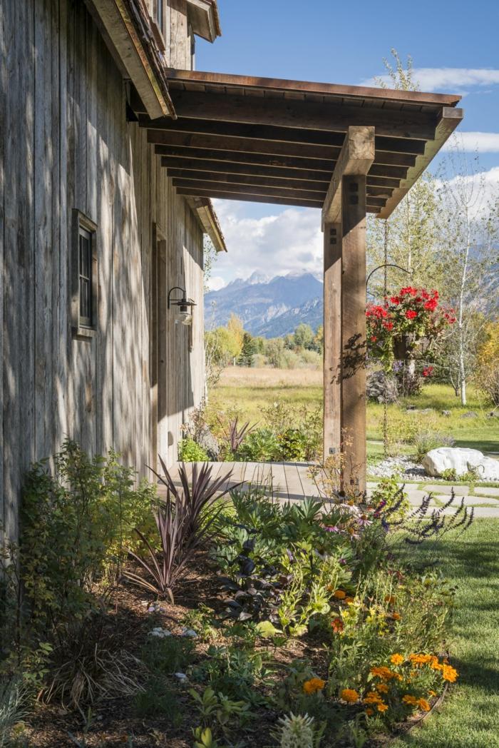 ein Garten mit bunten Blumen, ein Haus aus Holz, hängender Blumentopf, Garten verschönern