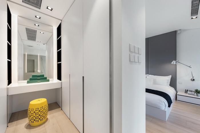 ein schlafzimmer mit einem bett mit einer weißen decke und mit kleinen und großen weißen kissen, eine graue lampe und eun boden aus holz, weiße wände mit lampen und mit einem großen spiegel, kleines schlafzimmer einrichten