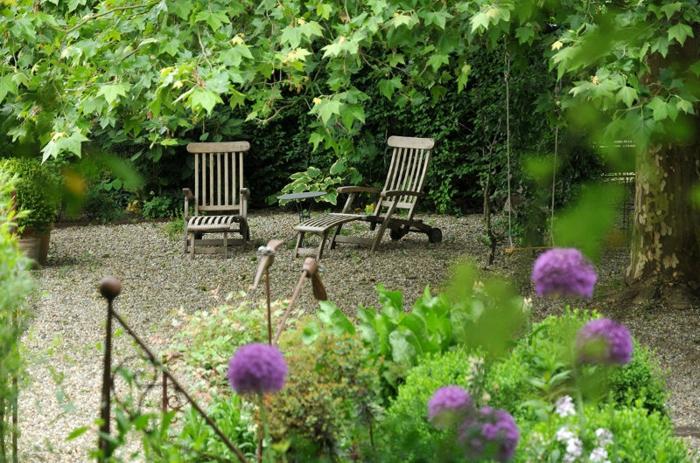 schöne und bequene Liegestühle, Kies am Boden, Schatten von den Bäumen, Garten verschönern