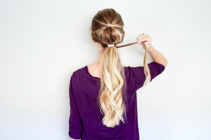 lockige haare, balayage blond, lila bluse mit langen ärmeln, halber pferdeschwanz binden