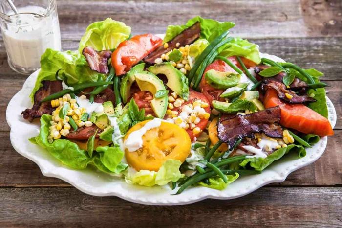 gesunde Salate, Kirschtomaten, Avocado, mit weißen Dressing bedeckt