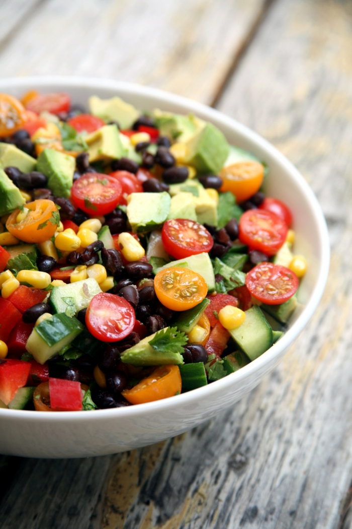 rote und gelbe Kirschtomate, Avocado, Korn und kleine Olive als Dekoration Salat Rezepte zum Abnehmen