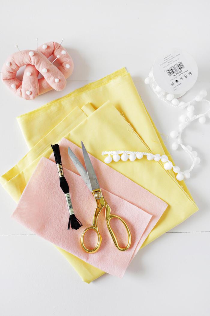 Materialien für DIY Projekt, süßes Kissen Katze, gelber und rosa Stoff, schwarzer Faden, weiße Pompons und Schere