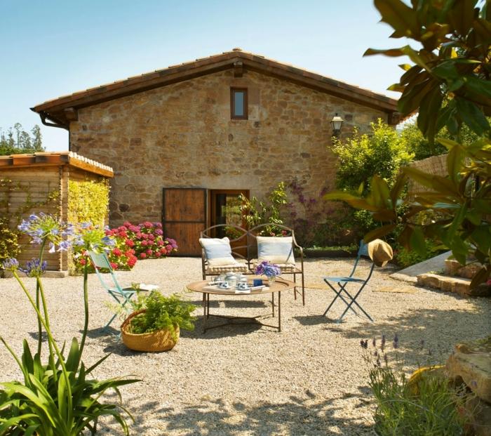 mit Kies belegter Boden, elegante Gartenmöbel, blaue Blumen, rote und lila Blumen, Ziersträuche, Garten verschönern
