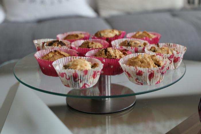 schöne rosa Dekorationen von Verpackungen voller Muffins auf Ständer aus Glas, Tischdeko Kommunion