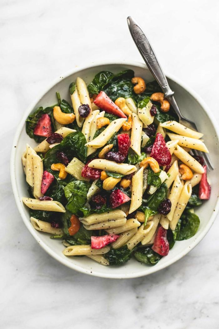 leckere Nudeln, gelbe Kaschunüsse, grüne Blätter, rote Erdbeere, Salat Rezepte zum Abnehmen