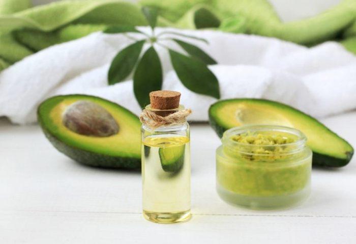 öl für die haare, avocadohälten, weißer tuch, grüne blätter, kosmetikbehälter mit selbstgemachter haarkur mit avocadoöl