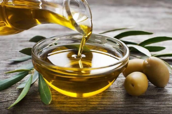 olivenöl haare, grüne oliven, kanne mit öl, olivenbläter, zwig, öl gießen, schüssel aus glas