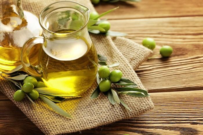 olivenöl haare, grüne oliven, kanne mit öl, leinen, hölterner tischm grüne blätter